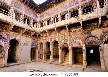 MANDAWA, INDIA - FEB 7, 2015: Historical mansion Havely yard with broken murals on the walls on February 7, 2015 in Rajasthan. With population of 21000 Mandawa is popular site with naive art Havelis homes