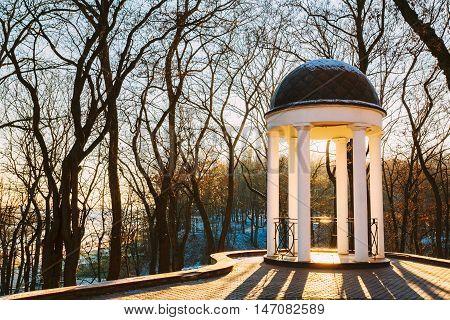 Sun At Sunset Shining Through Gazebo In City Park In Gomel, Belarus. Garden Pergola