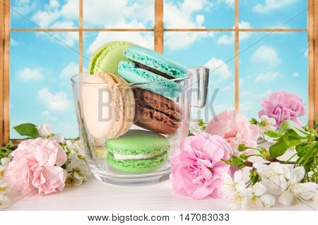French macaroons of different colors in cup. Turquoise chocolate and green macaroons on a background of a window.