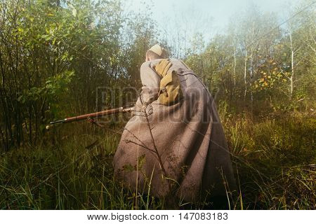 Unidentified re-enactor dressed as Soviet russian soldier running with rifle in forest grass in fog