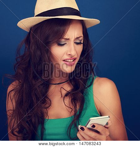 Unhappy Angry Woman In Hat Looking On Mobile Phone In Stress Emotion On Blue Background. Closeup Por