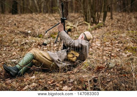 Pribor, Belarus - April 04, 2015: Unidentified re-enactor dressed as Soviet russian soldier olled on ground with a machine gun