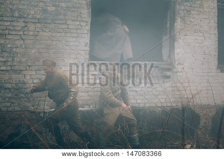 Pribor, Belarus - April 05, 2015: Unidentified re-enactor dressed as Soviet russian soldiers storming building
