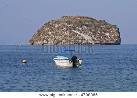 Small Boat Anchored With Island Background