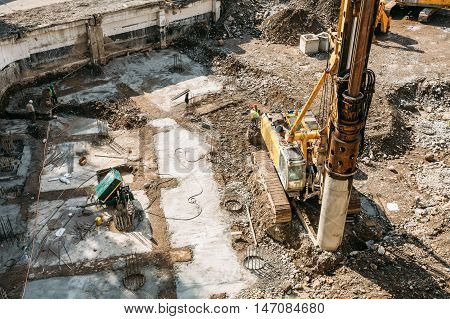Working Heavy Construction Equipment On A Construction Site. Laying The Foundation Of High-rise Apartment Building.