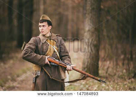 Pribor, Belarus - April 04, 2015: Young unidentified re-enactor dressed as Soviet soldier gunner goes along a forest road.