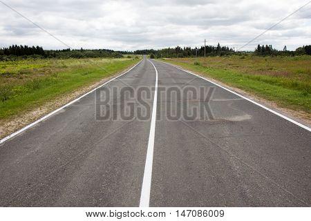 Endless empty asphalt road in Russian suburb