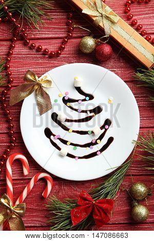 Chocolate Christmas Fir-tree On White Plate On Red Wooden Table