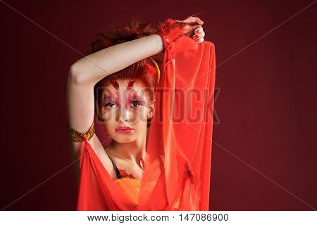 Phoenix woman. Young girl portrait red background