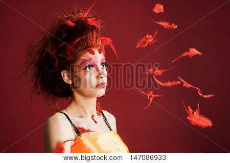 Phoenix woman. Young girl portrait and flying feathers red background
