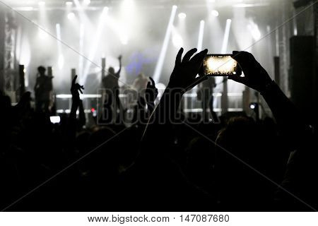 Silhouette of hands recording videos at music concert. Pop music concert with lights, smoke and lots of people