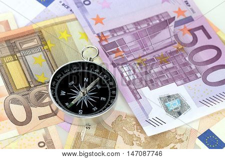 Assorted denominations of Euro bills with a compass on top of it