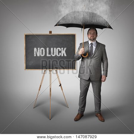 No luck text on blackboard with businessman and umbrella