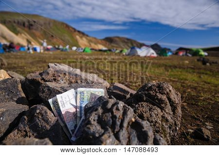 Icelandic currency are lying on the stones in Landmannalaugar, Iceland