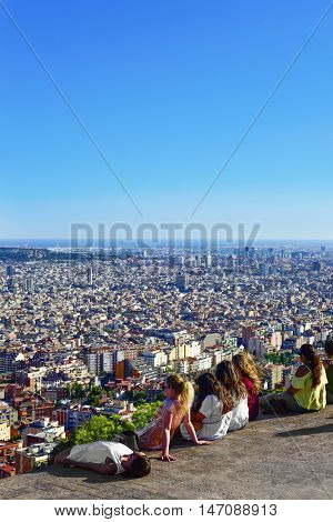 BARCELONA, SPAIN - AUGUST 15: People observing the city from above on August 15, 2016 in Barcelona, Spain. From the top of the hill, there is a wonderful view of the city