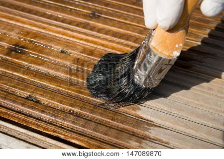 Close up of applying stain to a decking area