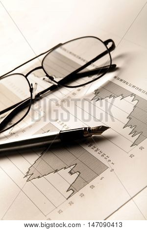 Fountain Pen And Glasses On Financial Graphs Close-up