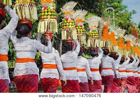 Procession of beautiful Balinese women in traditional costumes - sarong carry offering on heads for Hindu ceremony. Arts festival culture of Bali island and Indonesia people Asian travel background