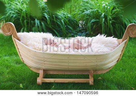 Wooden cradle in the form of the boat on a green grass. The baby lies on a white fluffy blanket