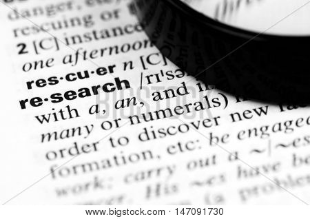 Close Up of Specific Word Research in a Dictionary with Loupe