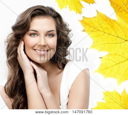 beauty closeup portrait of attractive caucasian smiling woman brunette isolated on white studio shot lips toothy smile face hair head and shoulders looking at camera tooth hands yellow autumn leaves