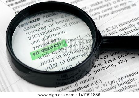 Close Up of  Highlighting Specific Word Research in a Dictionary with Loupe
