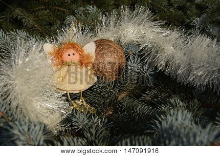 Christmas toy in the form of an angel and a sphere. Toys are located on a fir-tree. An angel in white clothes. Sphere of gold color