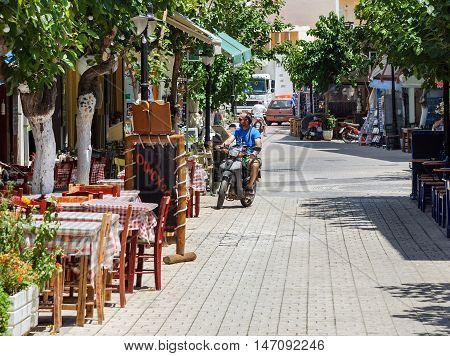 PALEOCHORA, CRETE, GREECE - JUNE 2016: Motorcyclist is driving at street of Paleochora town on Crete island, Greece