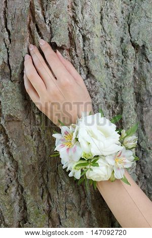 White wrist corsage of lisianthus (eustoma) and alstroemeria flowers on a hand