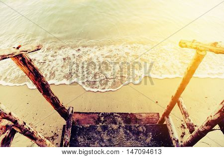 Vintage landscape nature background Wooden railing with sand beach and motion blur of the water on the sea in morning light