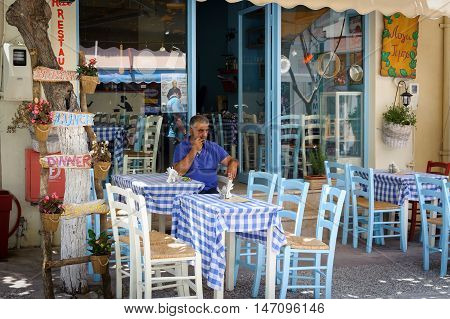 PALEOCHORA, CRETE, GREECE - JUNE 2016: Man sitting at traditional Greek tavern at Paleochora town on Crete island