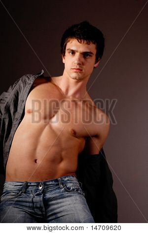 Studio portrait of handsome man showing his muscles