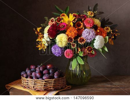 Still life with autumn bouquet of garden flowers in a vase and plums in the basket.