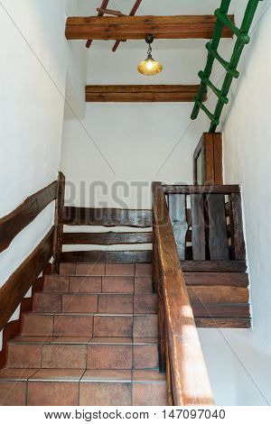 Decorative stairs from floor tiles and wooden railings, with a platform on top