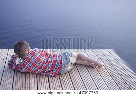 boy lies on a wooden pier near the water. boy in a plaid shirt and shorts lying on a wooden pier. view from the back. empty space for your text