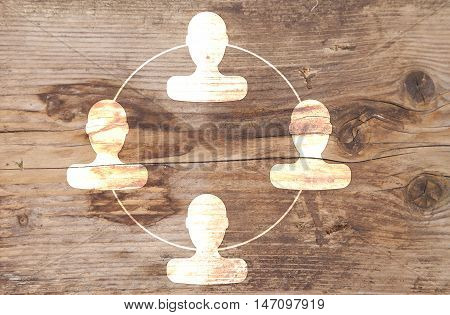 Organigram with heads on brown wooden background