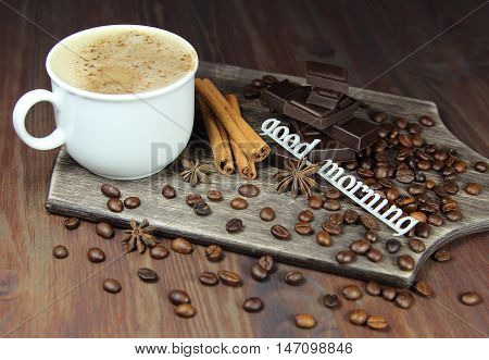 cup of coffee with chocolate, coffee grains, an anisetree, cinnamon and the inscription good morning