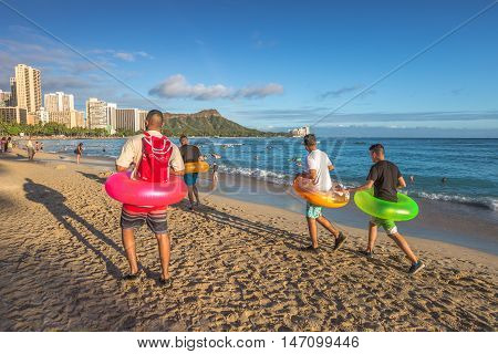Waikiki, Oahu, Hawaii - August 18, 2016: young tourists walking on the shore wearing the colorful rubber ring at Waikiki beach in Honolulu. The colored ring pools are very popular in Hawaii.