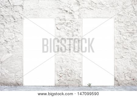 Two vertical empty posters on an old white wall. Street advertising billboards with space for you advertisement text or promotion. Advertisement concept. White empty posters on the building wall