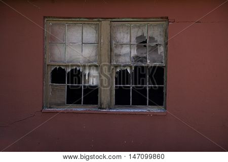 Old abandoned building with broken window panes.