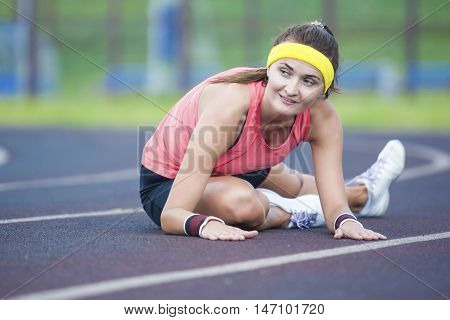 Sport Concepts and Ideas. Caucasian Brunette Female in Athletic Sportgear Having Legs Stretching Excercises Outdoors. Horizontal Shot