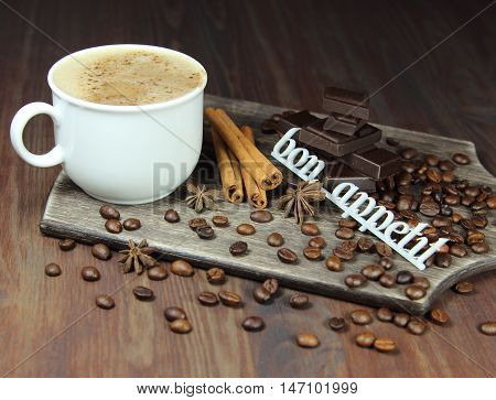 cup of coffee with chocolate, coffee grains, an anisetree, cinnamon and the inscription bon appetit