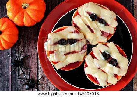 Halloween Mummy Mini Pizzas On Black And Orange Plate Over Rustic Wood Background