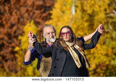 Happy elderly couple enjoying life in a bright sunny autumn day