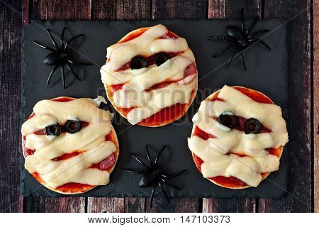 Halloween Mummy Mini Pizzas On Slate Server With Spiders