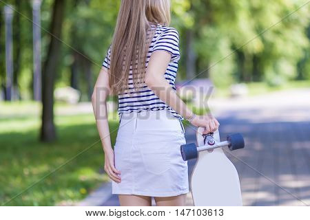 Female Blond Teenager Back View. Posing With Longboard Outdoors. Horizontal Image Orientation