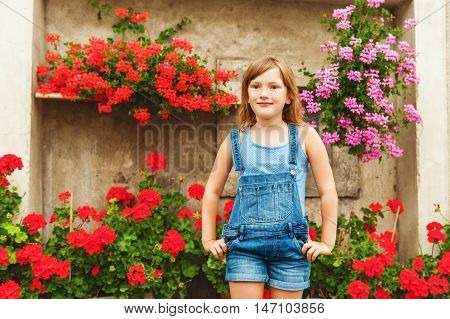 Summer portrait of a little girl of 6 years old, wearing denim overalls