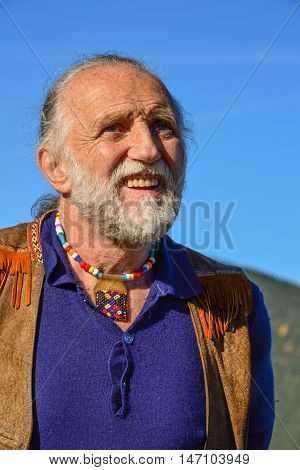 Porrait of impressive elderly man dressed in hippie style against blue sky in a bright sunny autumn day