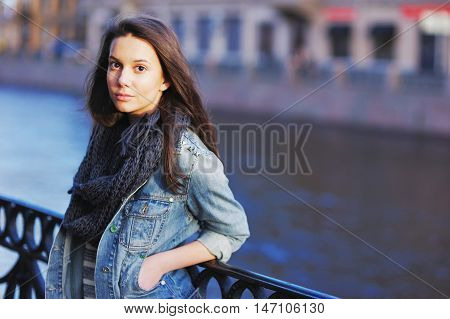 Beautiful Girl In Blue Jeans Jacket And Scarf Straightens Hair Standing Near The Parapet On The Emba