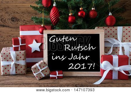 Colorful Card For Seasons Greetings. Christmas Tree With Red Balls. Gifts Or Presents In The Front Of Wooden Background. Chalkboard With German Text Guten Rutsch Ins Jahr 2017 Means Happy New Year